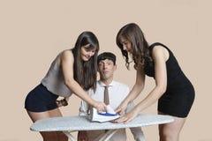Junge Frauen, welche die Bindung des entsetzten Mannes über farbigem Hintergrund bügeln Stockbilder