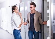 Junge freudige Paare, die neuen Kühlschrank im Grossmarkt wählen Lizenzfreies Stockfoto