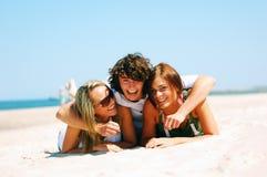 Junge Freunde auf dem Sommerstrand Lizenzfreie Stockfotos
