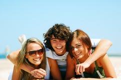 Junge Freunde auf dem Sommerstrand Lizenzfreies Stockbild