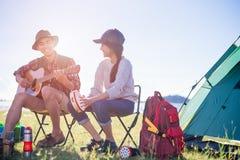 Junge Freunde der glücklichen Gruppe in der Campingzeltpartei, die das Spielen von m hat stockbild