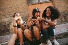 Junge Freunde, die auf dem Bürgersteig sitzen und Pizza essen lizenzfreie stockfotos