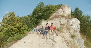 Junge Freunde, die auf der Klippe sitzen und Erholung in der Natur genießen stock video footage