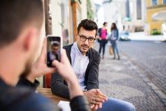 Junge Freunde, die in einem Café im Freien, ein Foto machend sitzen stockfotografie