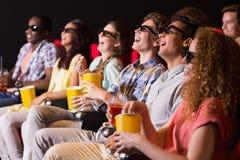 Junge Freunde, die einen Film 3d aufpassen Stockfotografie