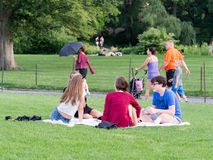 Junge Freunde, die am großen Rasen am Central Park in Manhattan kampieren Stockbilder