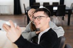 Junge Freunde, die mit Handy in einem Café sich fotografieren stockfoto