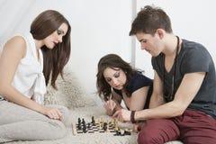 Junge Freunde, die Schach auf Sofa spielen Stockfotos
