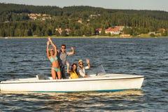 Junge Freunde, die Sommer auf Geschwindigkeitsboot genießen lizenzfreie stockbilder