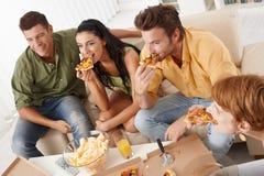 Junge Freunde, die zu Hause Pizza essen stockbilder