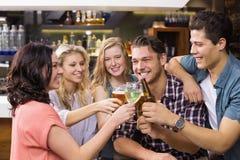 Junge Freunde, die zusammen etwas trinken Stockfotos