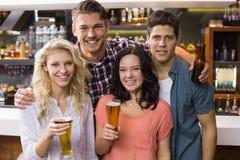 Junge Freunde, die zusammen etwas trinken Stockbilder