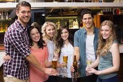 Junge Freunde, die zusammen etwas trinken Lizenzfreie Stockfotografie