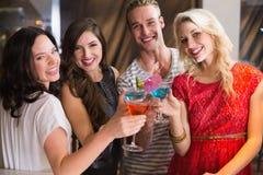 Junge Freunde, die zusammen etwas trinken Stockfotografie