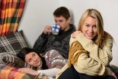 Junge Freunde geben gemütliches Häuschen des Winterurlaubs aus Stockfoto