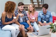 Junge Freunde mit den Getränken, die auf Sofa sitzen Stockfoto