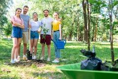 junge Freunde mit Gießkanne und Schaufel neue Bäume pflanzend lizenzfreies stockfoto