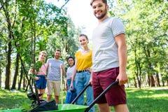 junge Freunde mit Schubkarre und dem neuen Baumfreiwillig erbieten stockfotografie