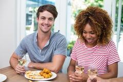 Junge Freunde mit Wein und Lebensmittel auf Tabelle Lizenzfreies Stockbild