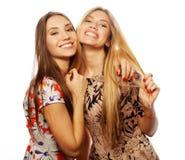junge Freundinnen im bunten Kleid auf weißem Hintergrund Stockfotografie