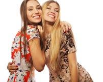 junge Freundinnen im bunten Kleid auf weißem Hintergrund Stockfoto