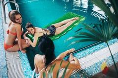 Junge Freundinnen, welche die Badebekleidung sich entspannt im sprechenden und lächelnden Schwimmbad tragen Stockfotografie