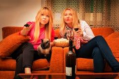2 junge Freundinnen zu Hause, die fernsehen und Weinretrostil trinken, filterten Bild Lizenzfreie Stockbilder