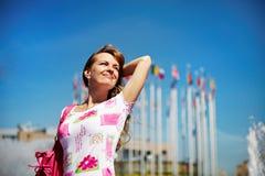 Junge freundliche Frau auf Hintergrund des Himmels Lizenzfreies Stockfoto