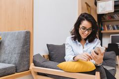 Junge frohe brunette Frau des Porträts in den schwarzen Gläsern, die auf Couch in der modernen Wohnung kühlen Unter Verwendung de stockbild