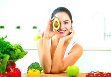 Junge frohe Frau der Schönheit, die frische Avocado hält lizenzfreies stockfoto