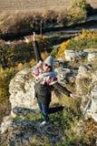 Junge frohe Frau, die in der Herbstausstattung, natürlicher Freien sce aufwirft Stockfotografie