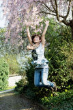 Junge frohe Frau springt unter blühenden Baum Stockfoto