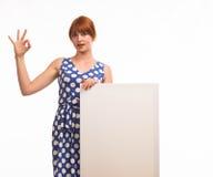 Junge frohe Frau, welche die Darstellung, zeigend auf Plakat zeigt Stockbilder