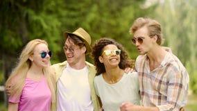 Junge frohe Freunde, die zusammen, gutes Wochenende im Park habend, Entspannung lachen lizenzfreies stockbild