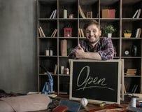 Junge frohe Mannlederarbeitskraft, die nahe offenem Zeichen am Holztisch steht Stockbild