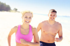 Junge frohe Paare, die entlang dem Strand rütteln Stockfotos