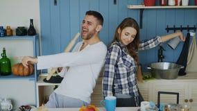 Junge frohe Paare haben Spaßtanzen und den Gesang, während sie zu Hause der Tabelle zum Frühstück in der Küche eingestellt werden Stockbild