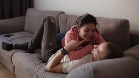 Junge frohe Paarentspannung, -umarmung und den Spaß haben, der auf dem Sofa im Wohnzimmer mit Dachbodeninnenraum liegt Spaß haben stock video footage