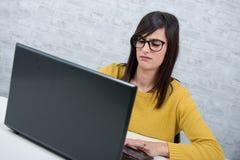 Junge frustrierte Frau, die mit Laptop arbeitet Lizenzfreie Stockfotografie