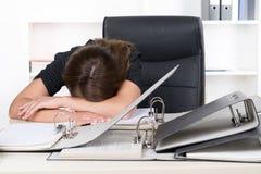 Junge frustrierte Frau liegt vor einem Stapel von Dateien Stockbild