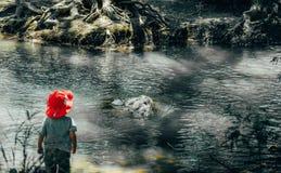 Junge am Fuß des Flusses stockbild