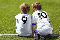 Junge Fußball-Fußball-Spieler Kleine Jungen, die auf Fußball-Neigung sitzen Lizenzfreie Stockfotos