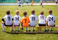 Junge Fußball-Spieler Junger Fußball Team Sitting auf Holzbank stockbild
