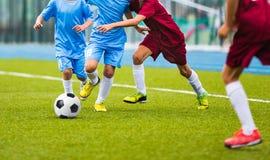 Junge Fußballspieler, die in Richtung zum Fußball laufen Fußballfußballspiel für Jugendteams lizenzfreies stockfoto
