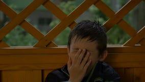 Junge gähnt im regnerischen Wetter, schläfriger Junge, Zeitlupe stock video footage
