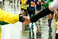 Junge geben seine Hand zu einem Läufer während des Marathons Lizenzfreies Stockfoto