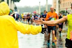 Junge geben seine Hand zu einem Läufer während des Marathons Lizenzfreie Stockfotos