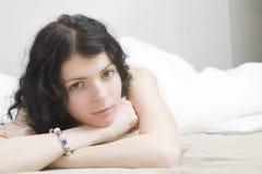 Junge gebohrte Brunettefrau, die sich auf Bett hinlegt Stockbild