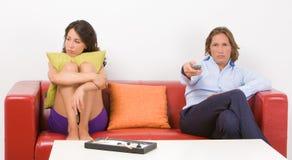 Junge gebohrte Paare, die auf dem Sofa in ihrem ho sitzen Lizenzfreie Stockfotografie
