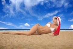 Junge gebräunte Frau, die auf dem Strand in weißem Bik liegt Stockfotos